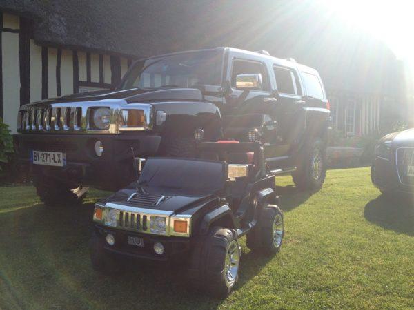 Voiture pour enfant Hummer électrique 12V devant un Hummer grandeur nature